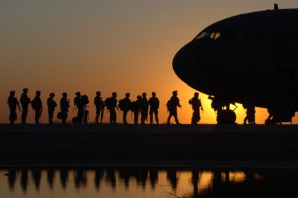 Silhouette of Soldiers boarding an aricraft